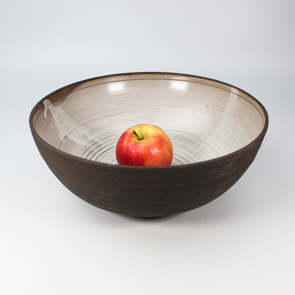 Large and deep pottery salad bowl with brown inner and off white inner. One apple inside dish.