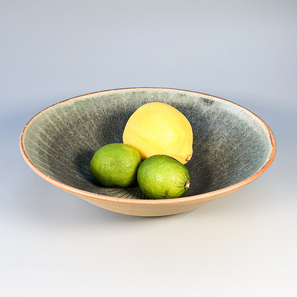 Medium size bowl with green sgraffito glaze containing one lemon and two limes