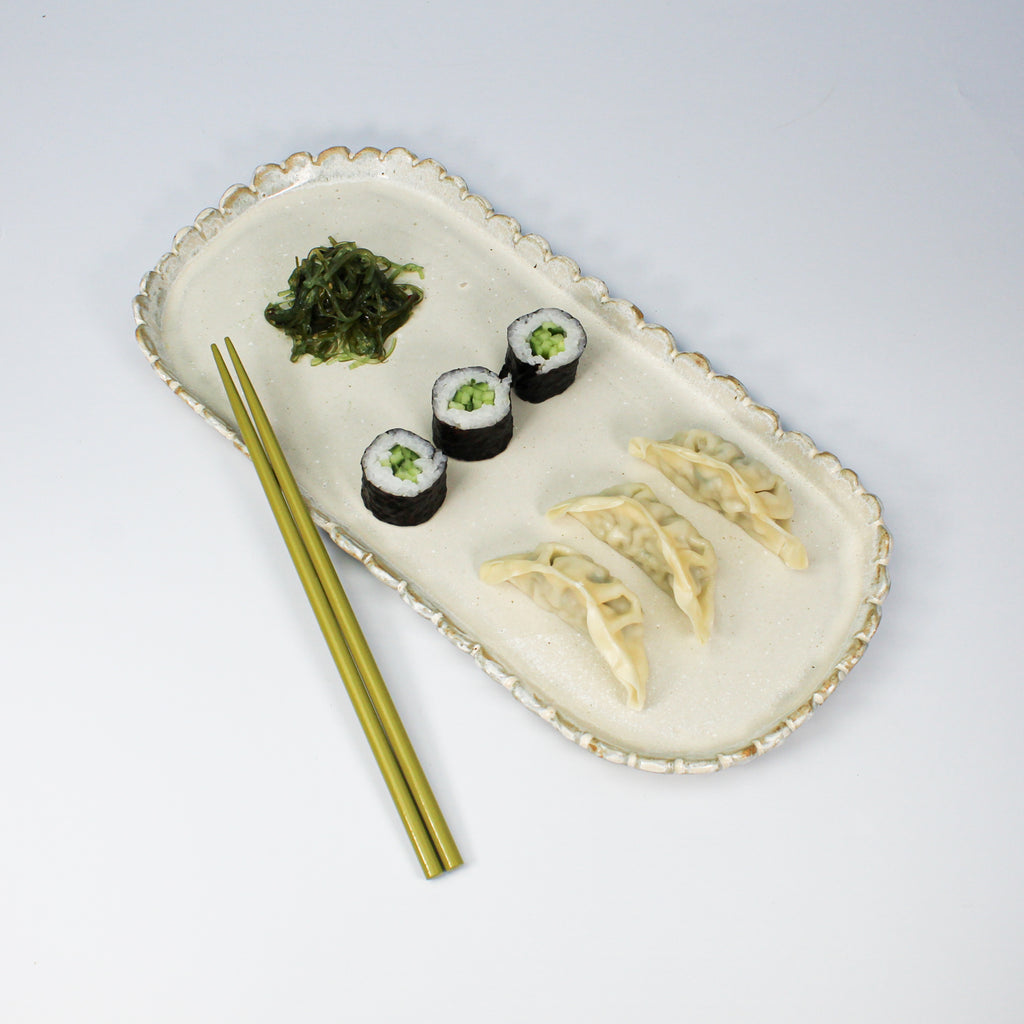 Pottery rectangular platter in off white. Scalloped edge with sushi on and chopsticks next to it.