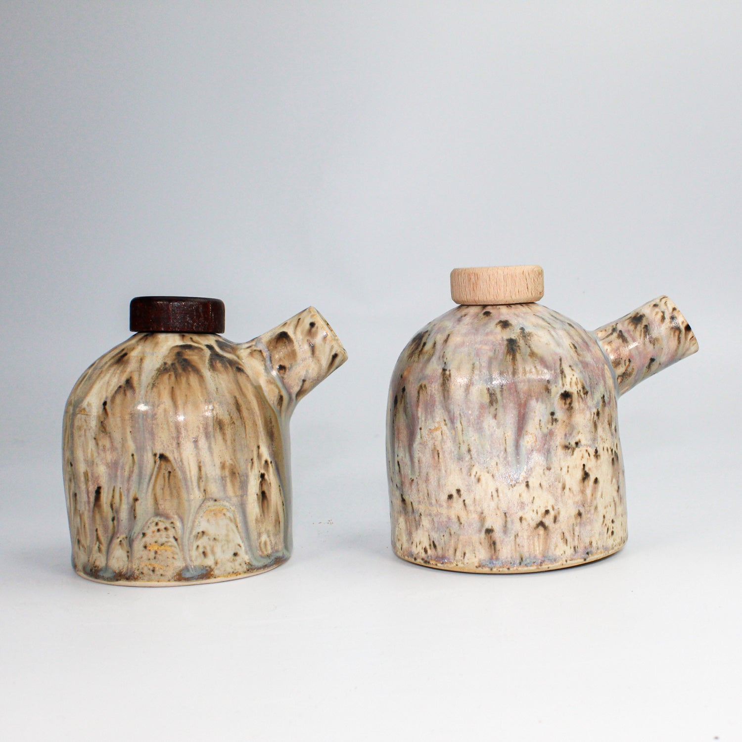 Pair of oil and vinegar pourers. Different coloured caps. Beautiful marbled glaze.
