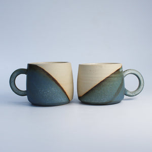 Two ceramic mugs with half white and half blue glaze