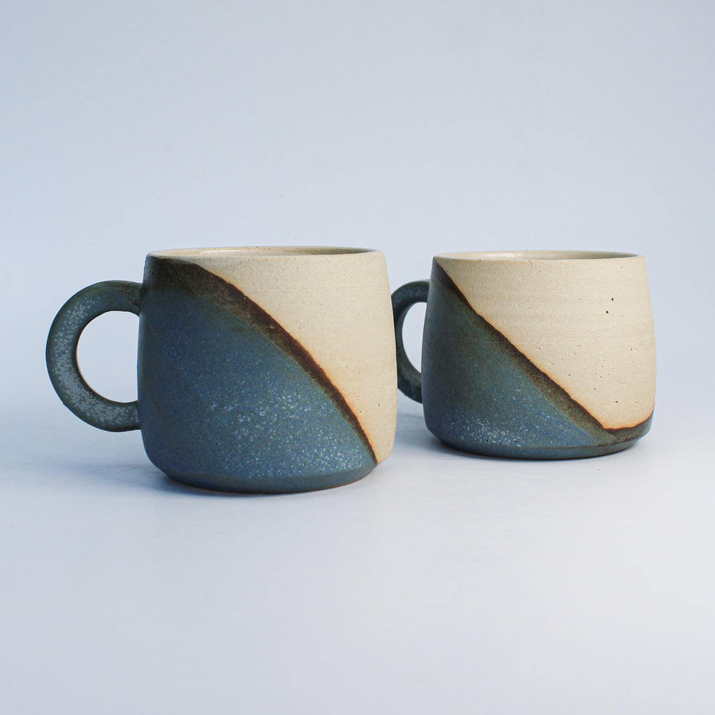 Pair of ceramic mugs in with half blue and half white glaze