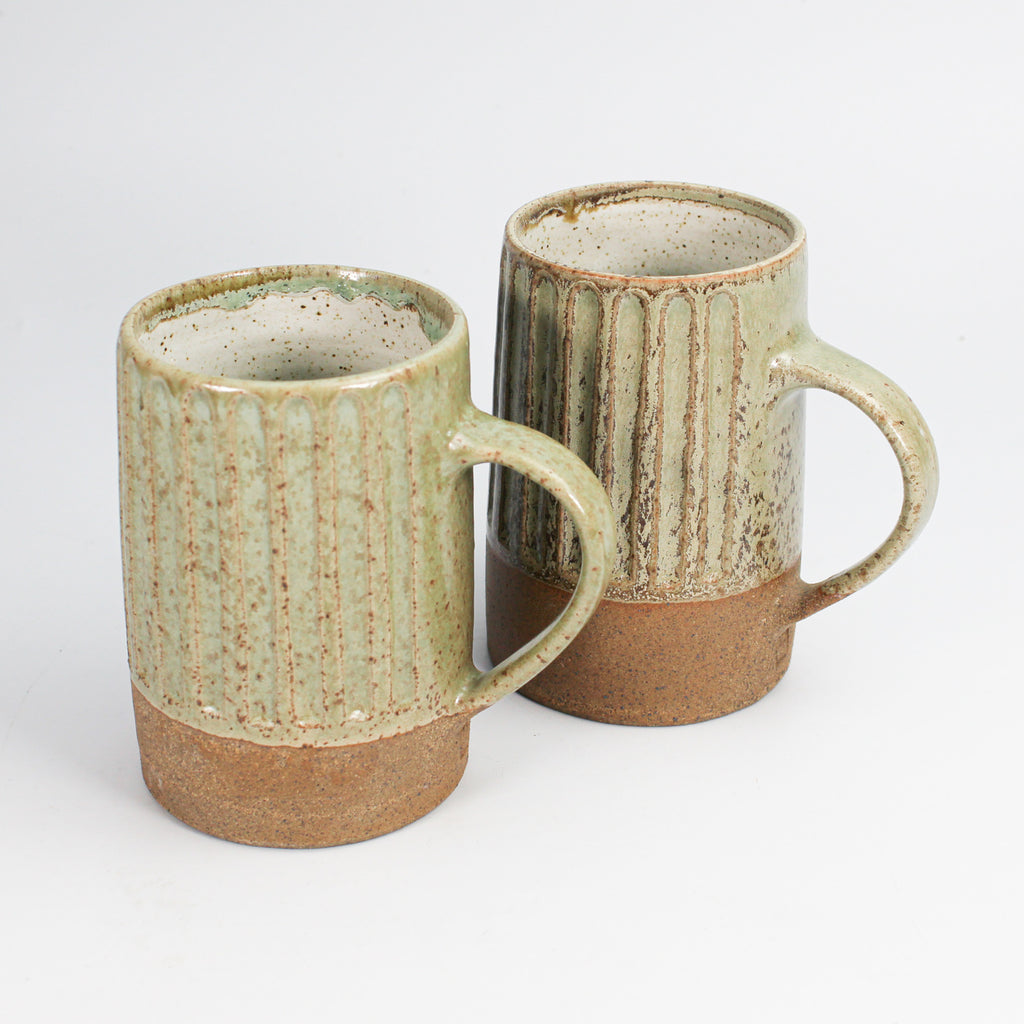 Two stoneware mugs. Brown at the bottom with vertical ridges above.