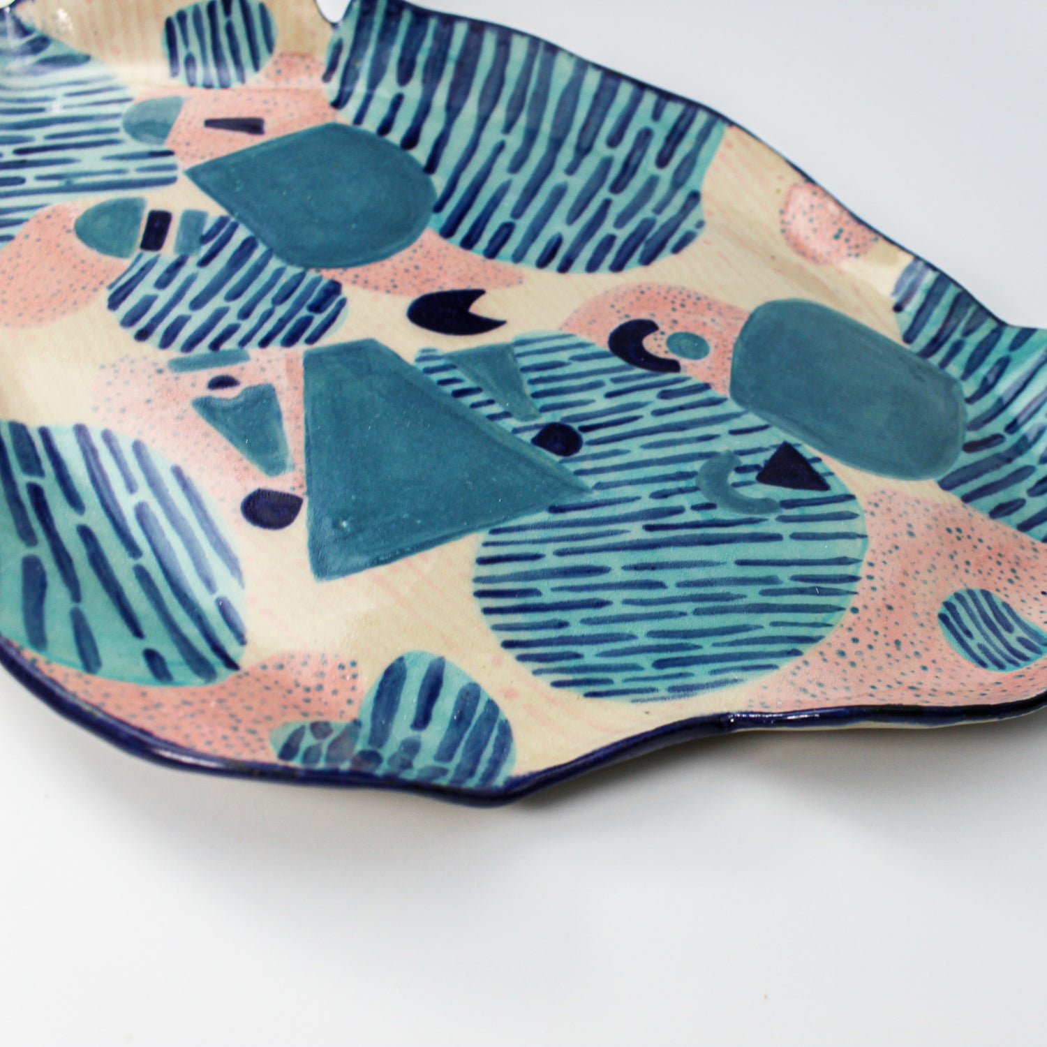 Side view of pink and blue pottery platter