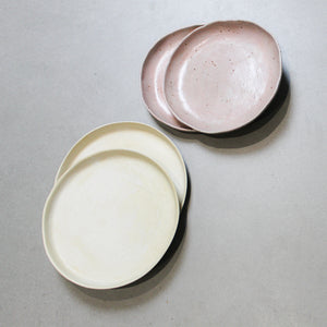 Pair of pink speckled ceramic side plates and pair of cream speckled side plates