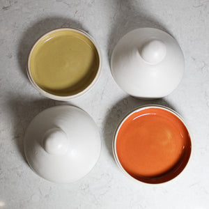 Two white butter dishes. Lids off. Inside of one dish is orange and the other is mustard. Dishes made of pottery.