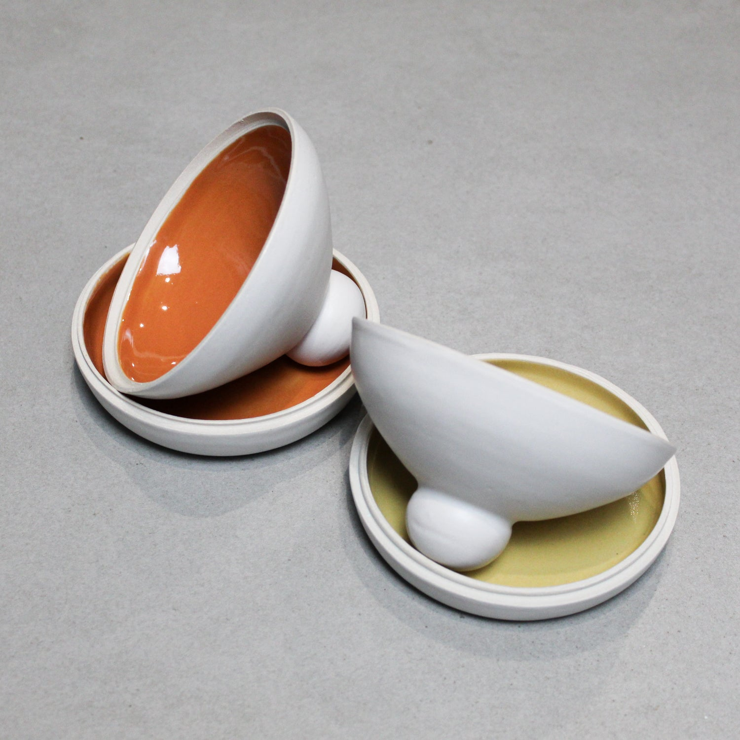 Two white pottery butter dishes. One has orange glazed inside and the other is mustard. The lids are off and inside the bases.