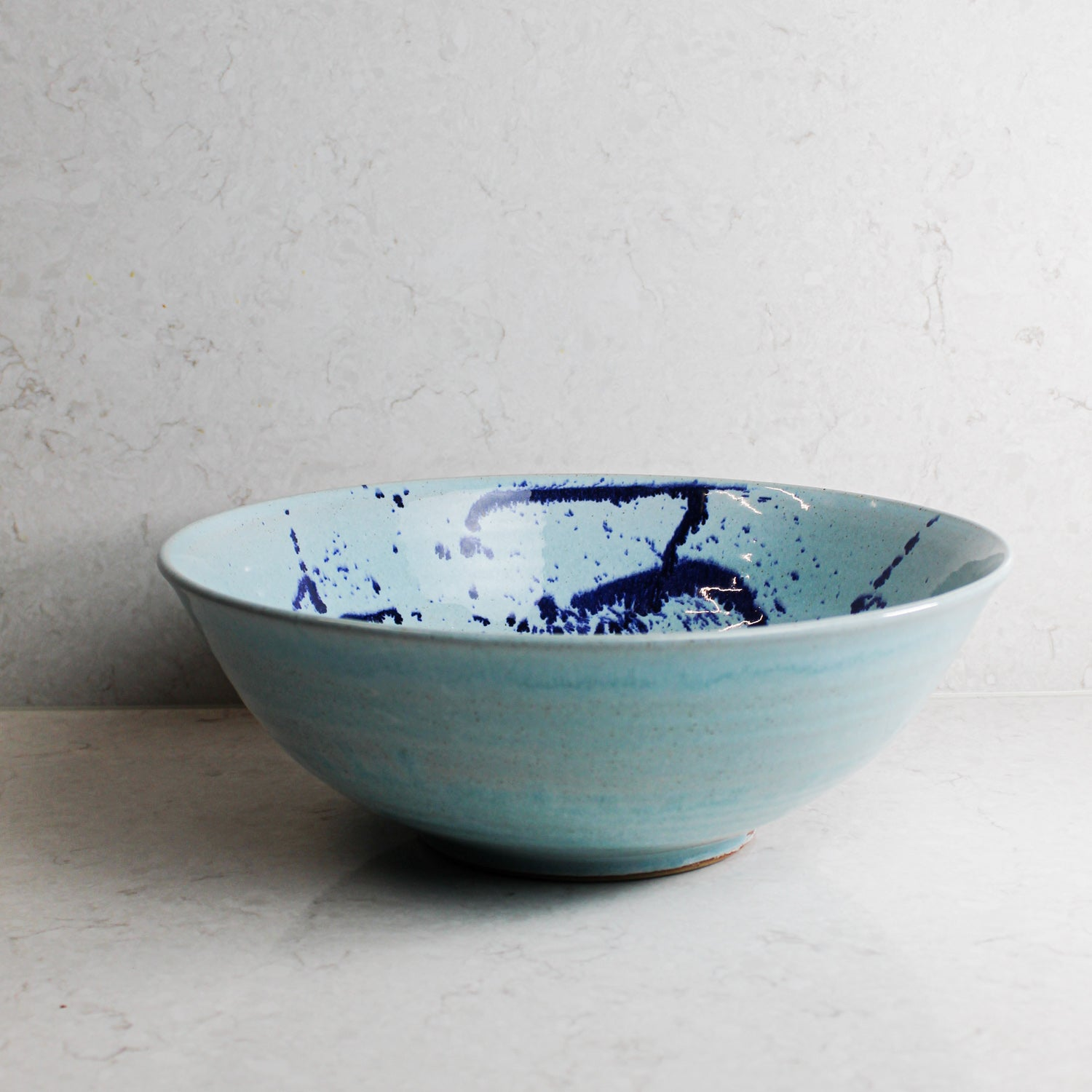 Side view of large baby blue ceramic salad bowl with darker blue splatters