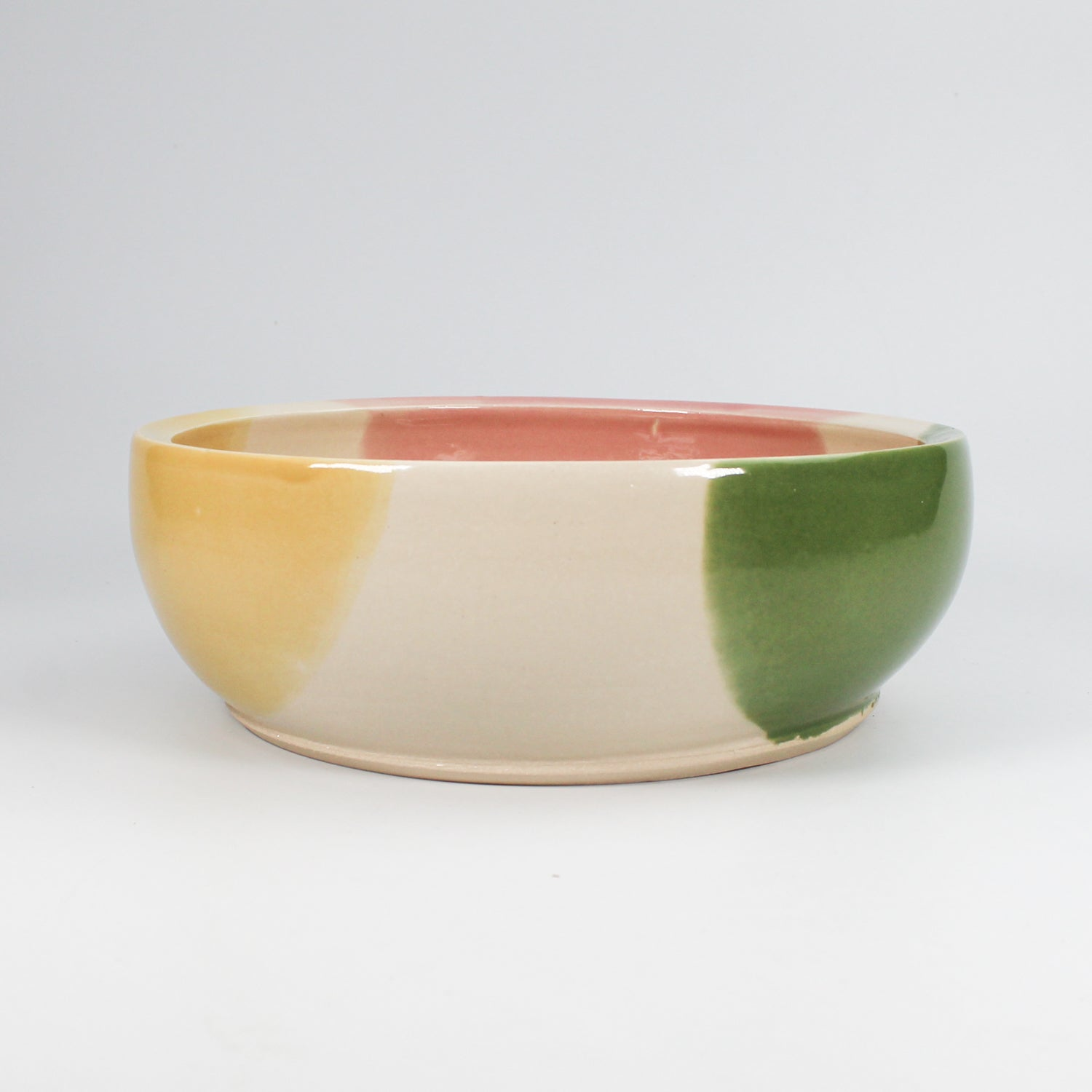 Side view of multi-coloured ceramic dog bowl with high gloss glaze