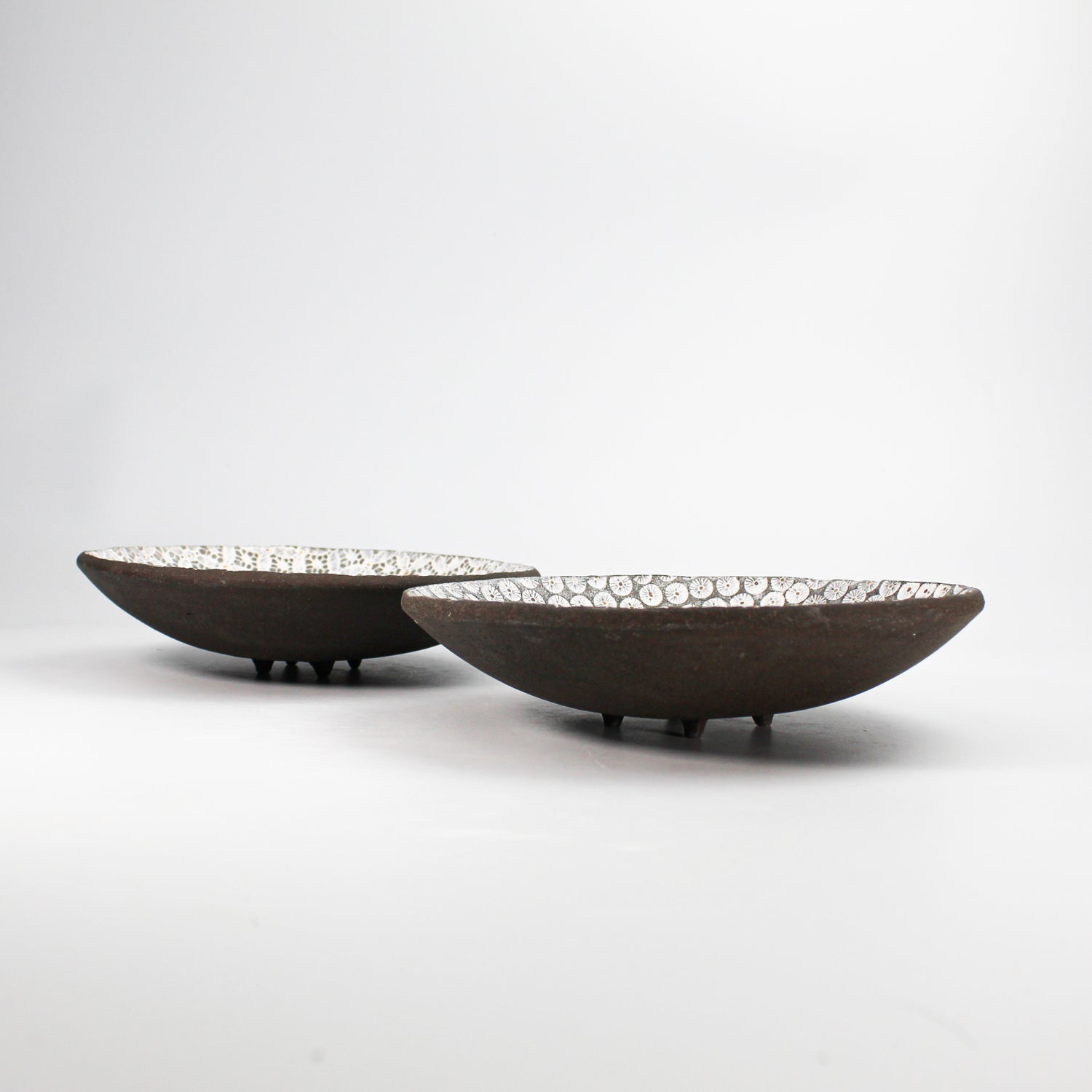 Side view of two dark brown pottery bowls with white glazed pattern