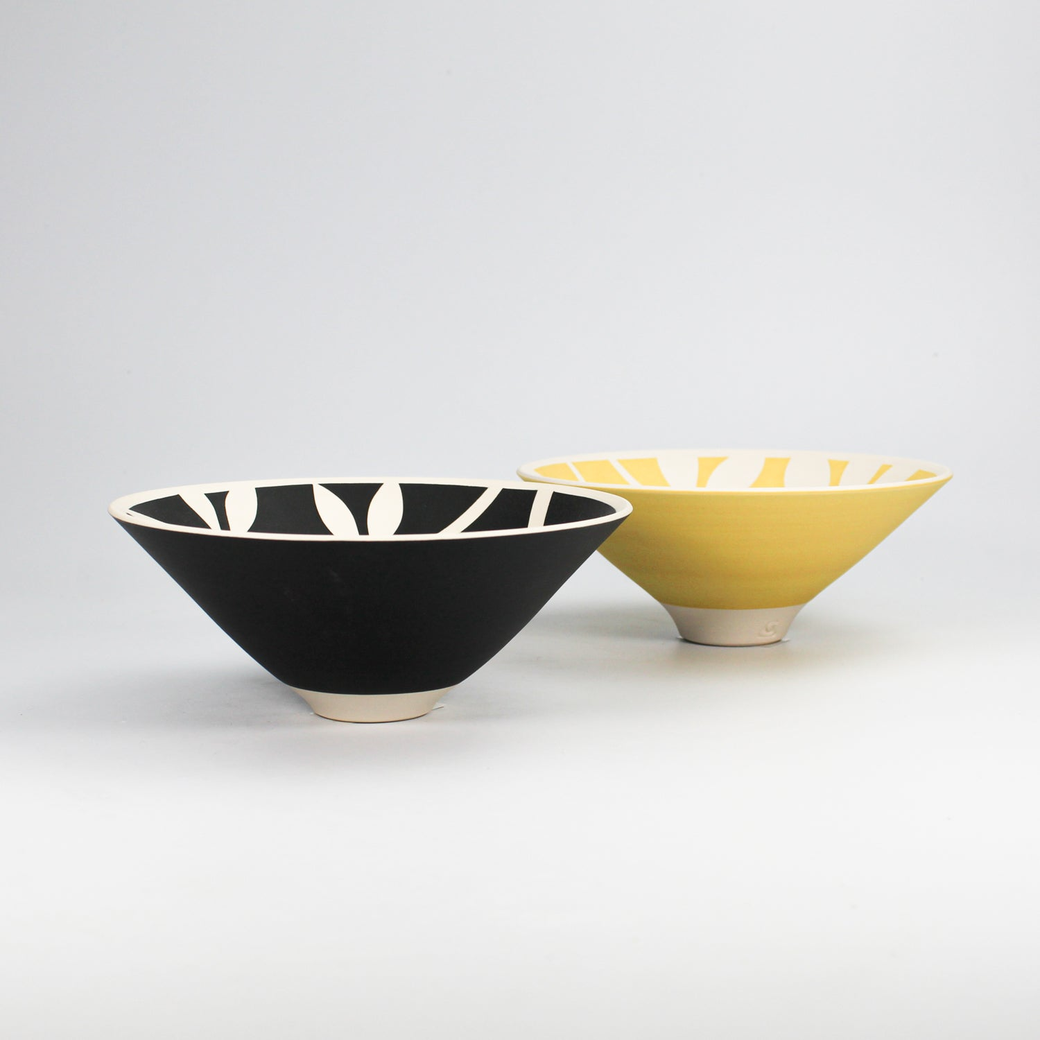 Side view of two porcelain bowls. One bowl is yellow and the other is black