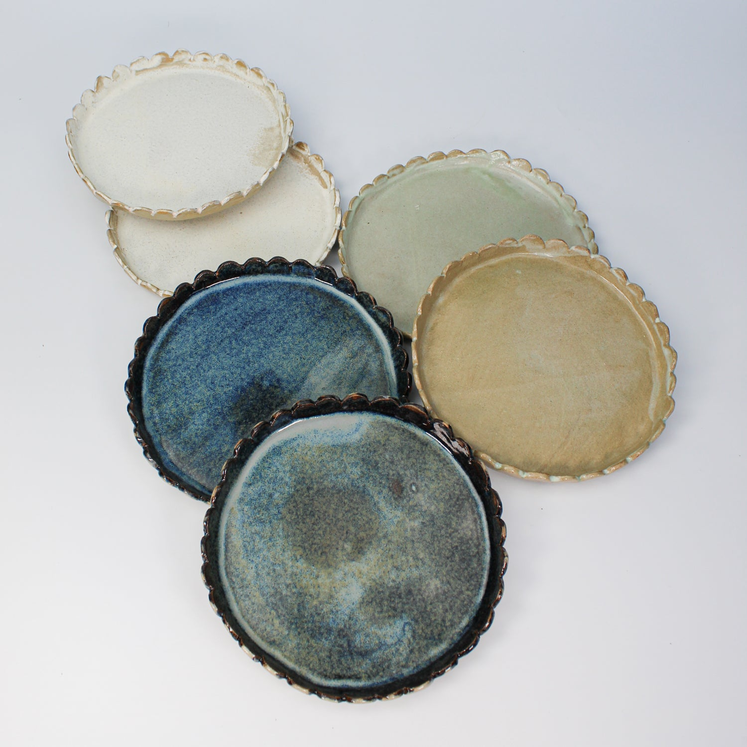 Six ceramic side plates with scalloped edges in blue, white and sage green.