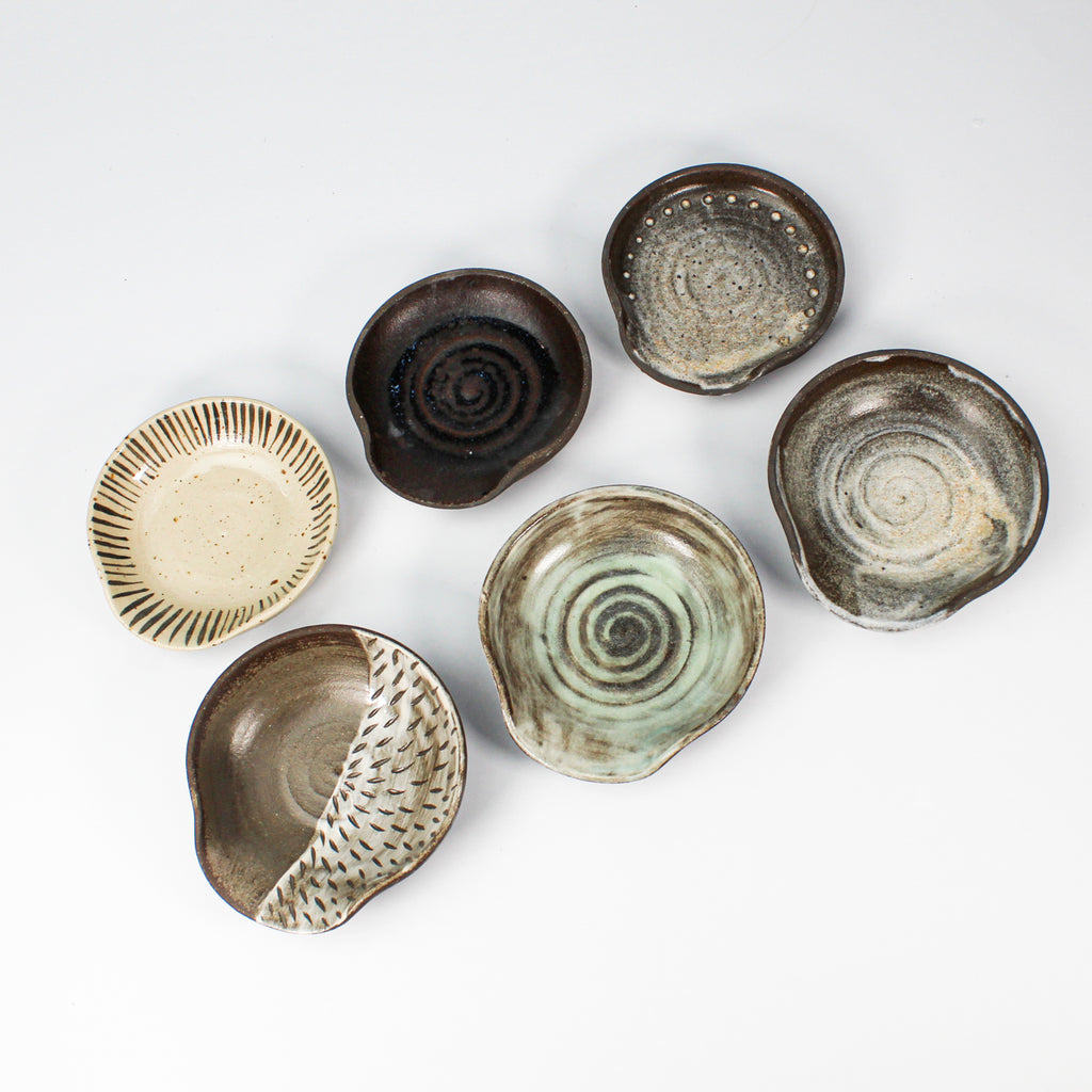 Six ceramic spoon rests in different coloured glazes.