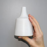Load image into Gallery viewer, Hand holding small off-white bottle vase