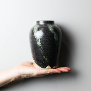 Small black and green pottery vase sitting in the palm of a hand