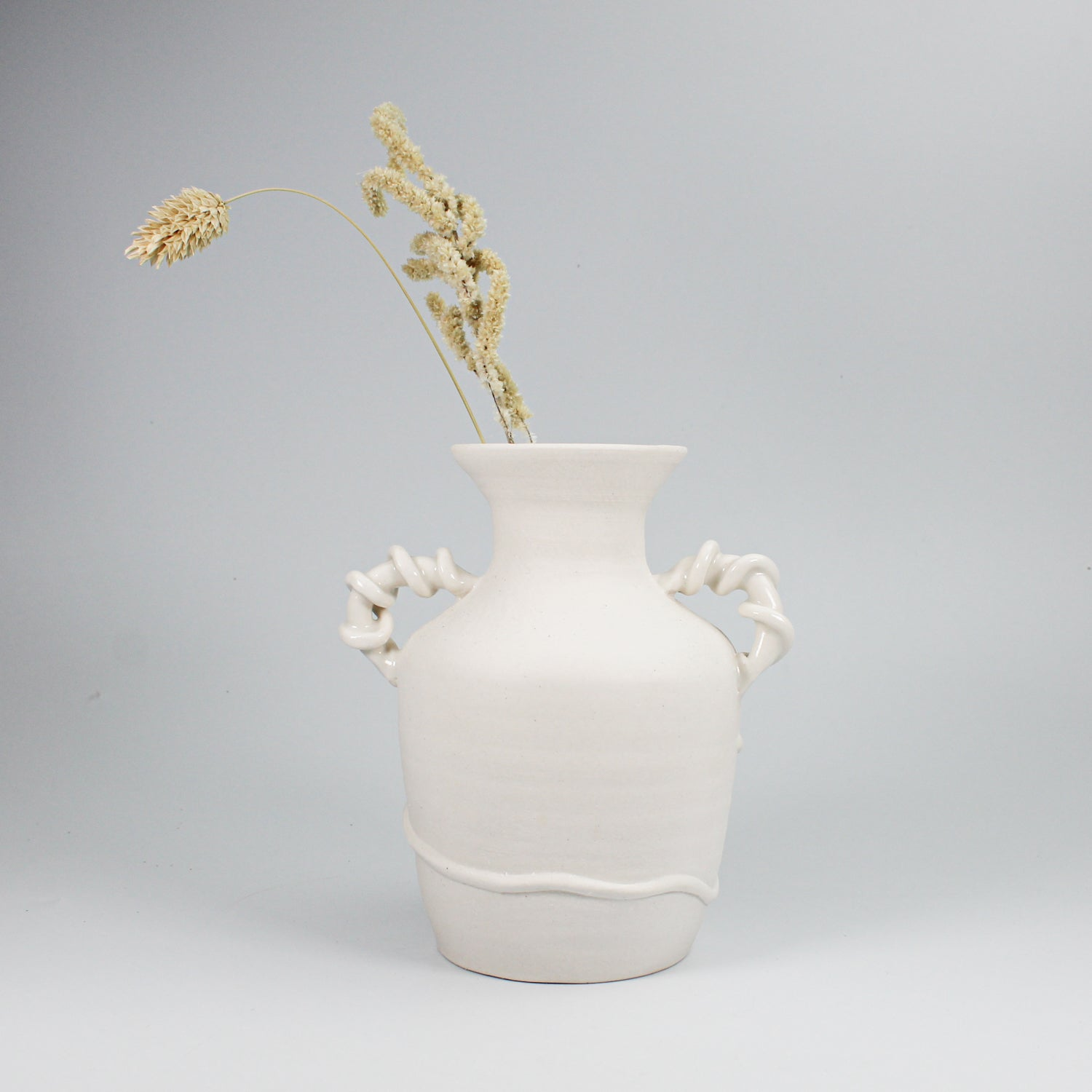 Ceramic small white vase with twisted handles. Handles are high gloss glazed, vase is matt glazed.