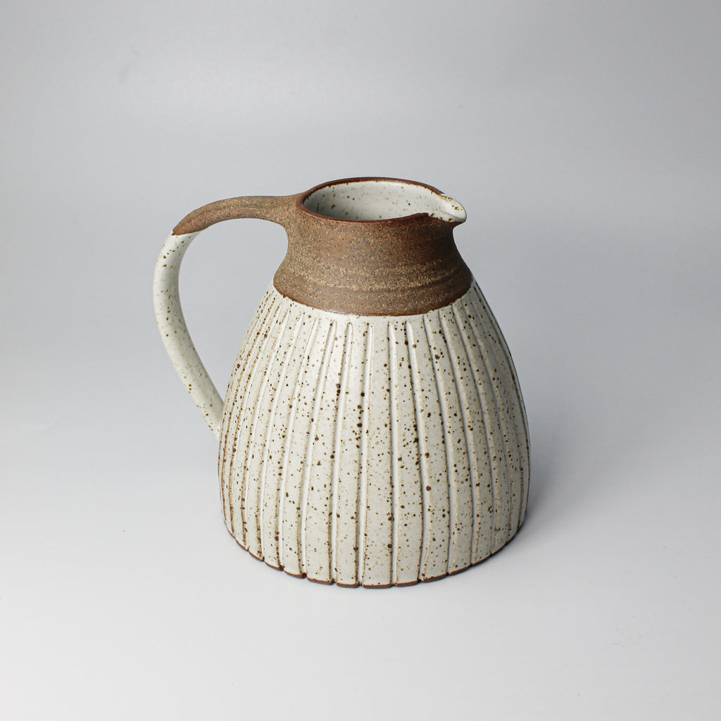Small white speckled and brown pottery jug