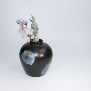Small black ceramic vase with blue detailing and dried flowers,