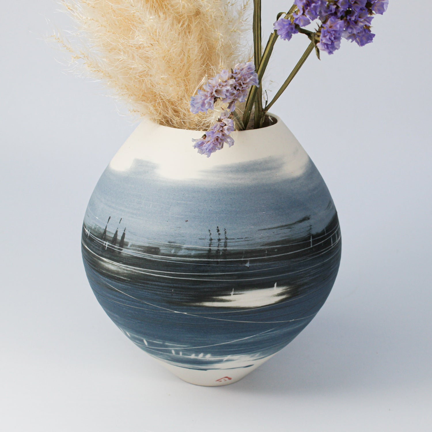 Blue and white porcelain spherical vase with fresh and dried flowers in