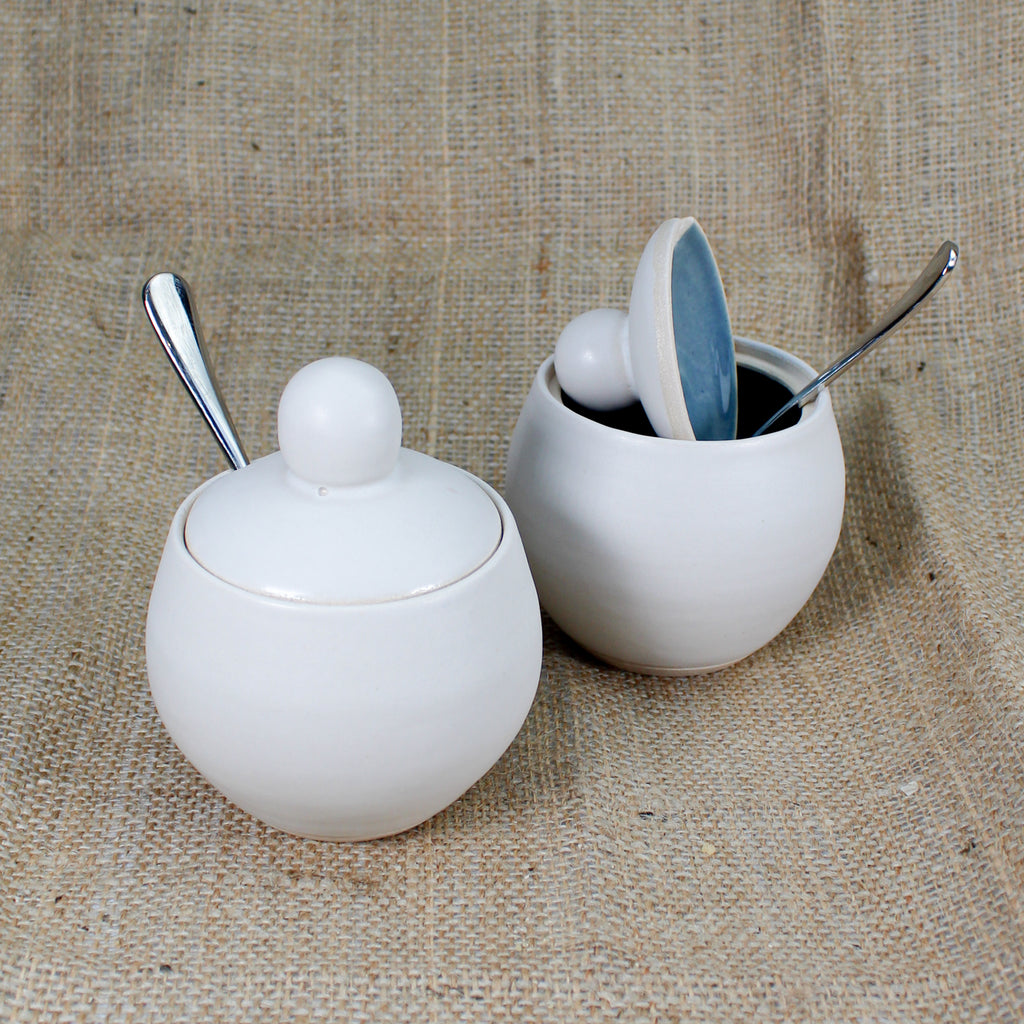 Two white ceramic sugar bowls with spoons in. Inside of one is blue gloss glazed