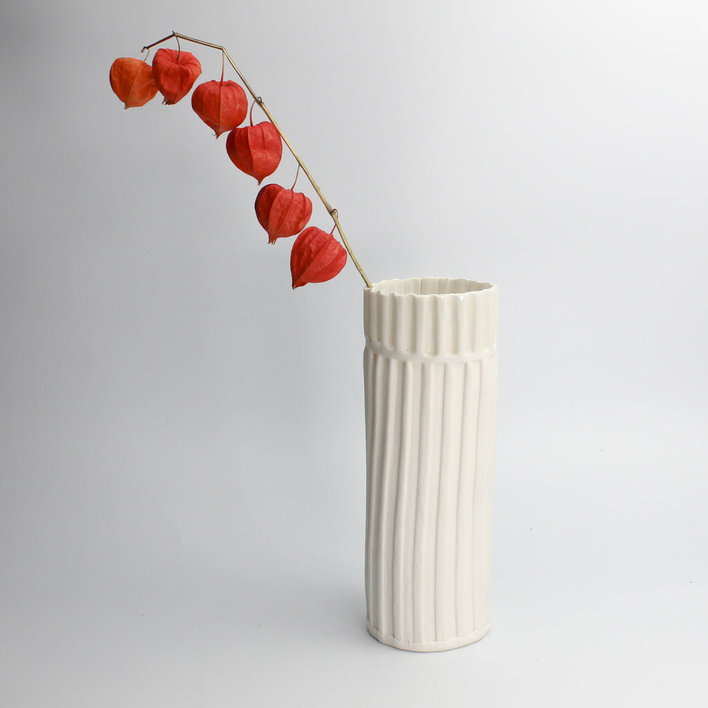 Partially glazed white porcelain tall vase with lantern flowers in it