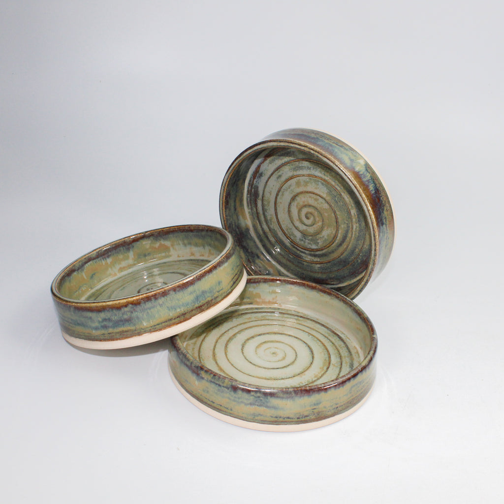 Three pottery tapas dishes. One stood on its side and one laying across the third one