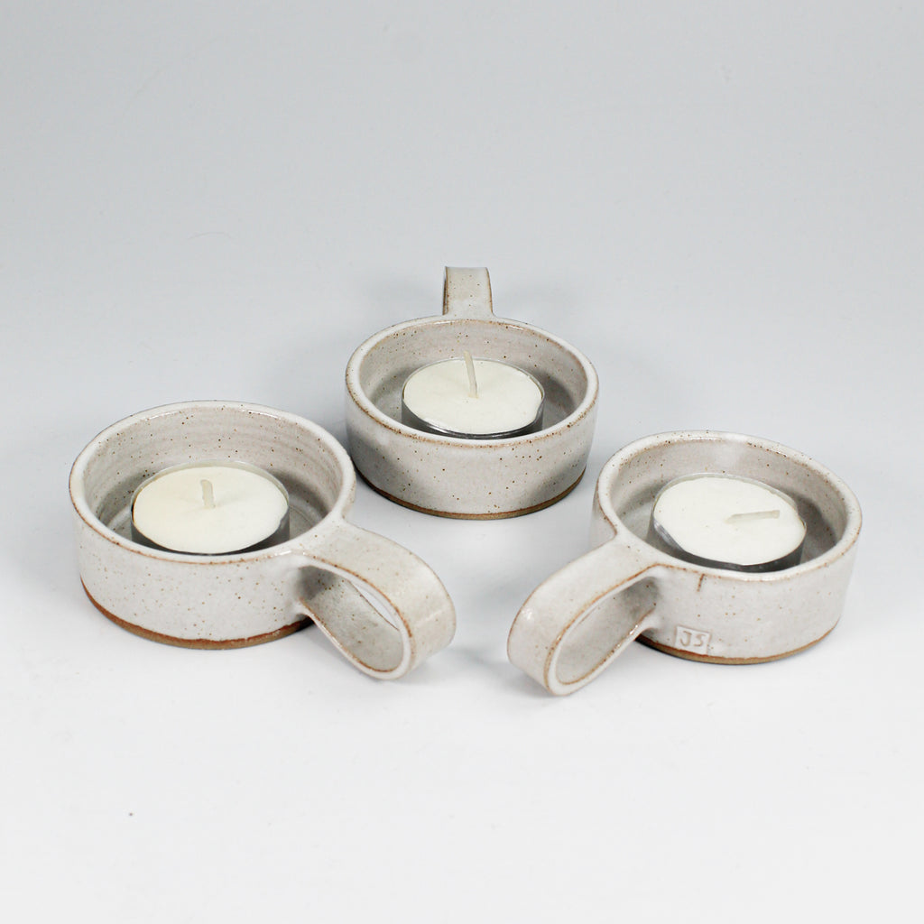 Trio of pottery tealight holders with handles all with tealights in