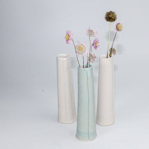 Trio of porcelain single stem vases. Two white, one with flowers in. One baby blue with flowers in.