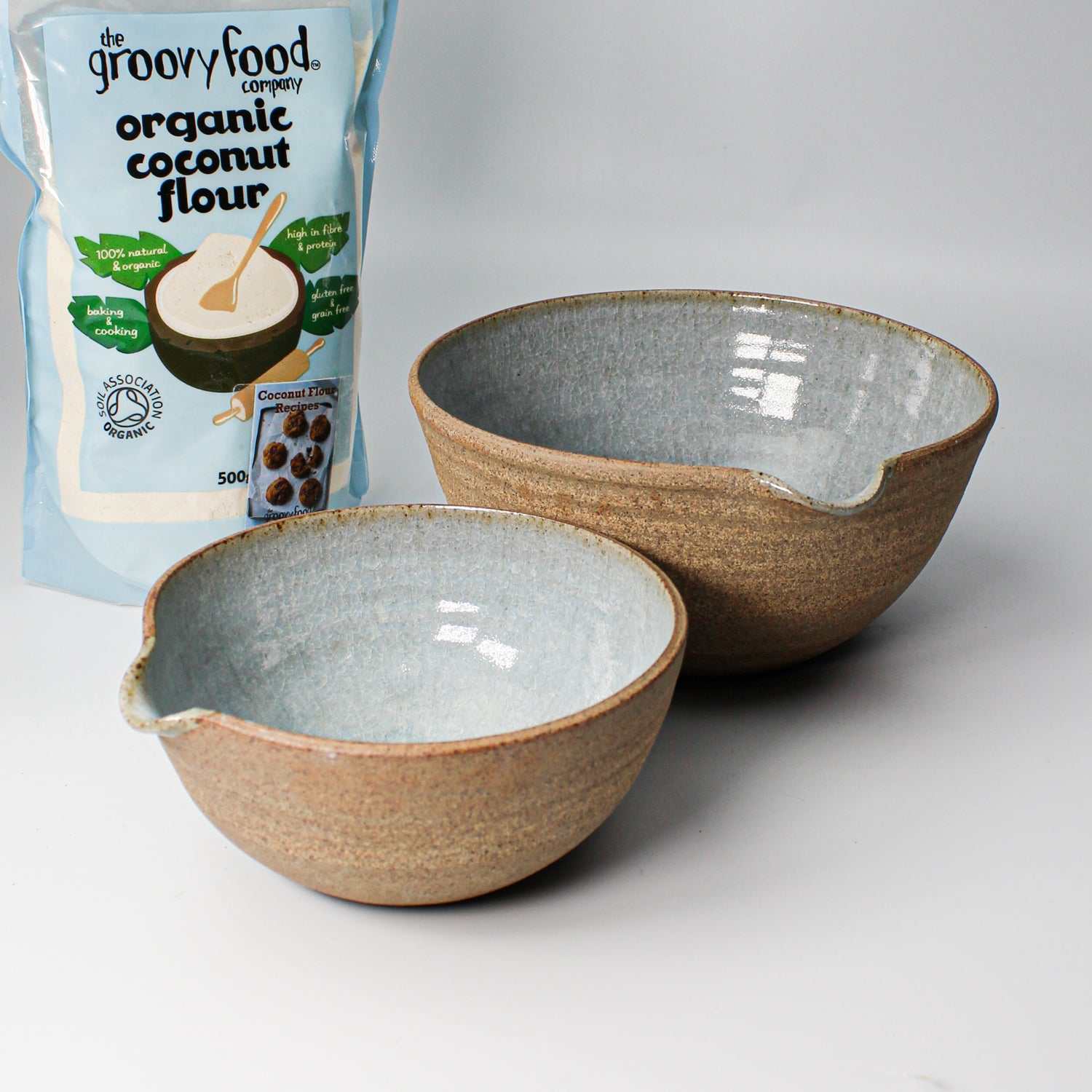 Two ceramic pouring boxes with blue inner glaze and external natural outer next to a bag of organic coconut flour