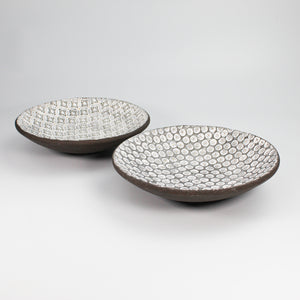 Two dark brown pottery bowls with different white glazed patterns.
