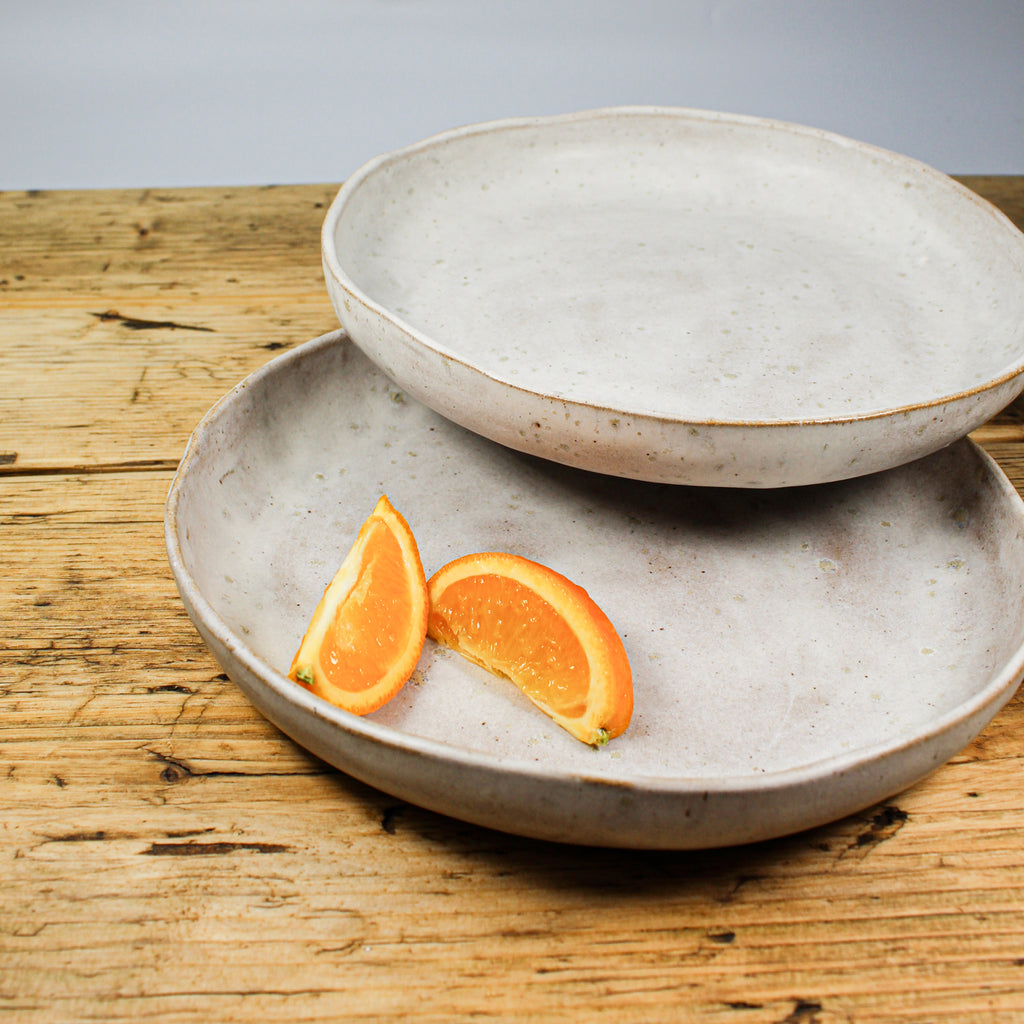 Two grey speckled pottery dishes with slices of orange on them. Sitting on wooden table.