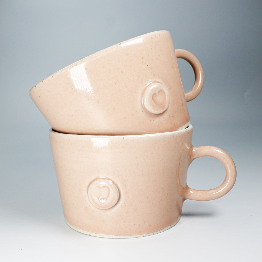 Two pink pottery mugs with heart motif stacked up