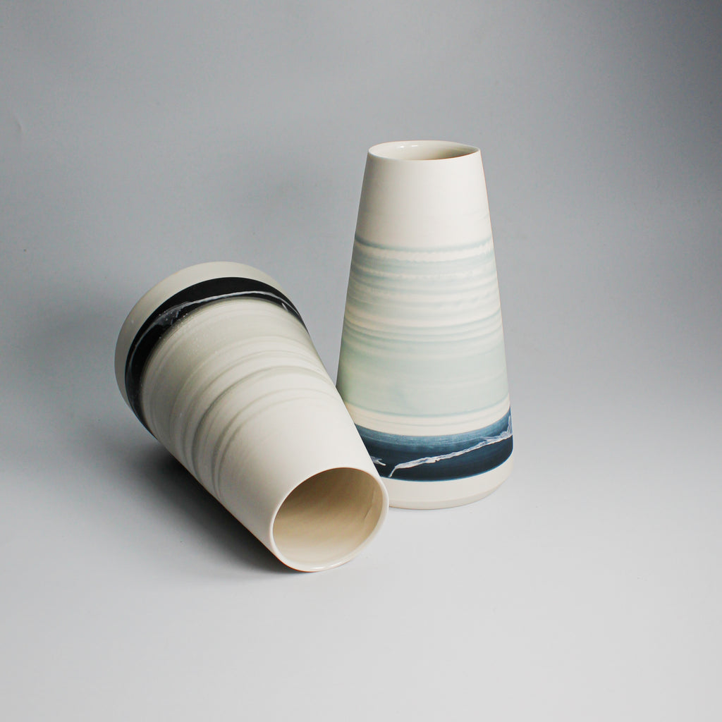 Two white conical porcelain vases with seascape patterns. One lying down