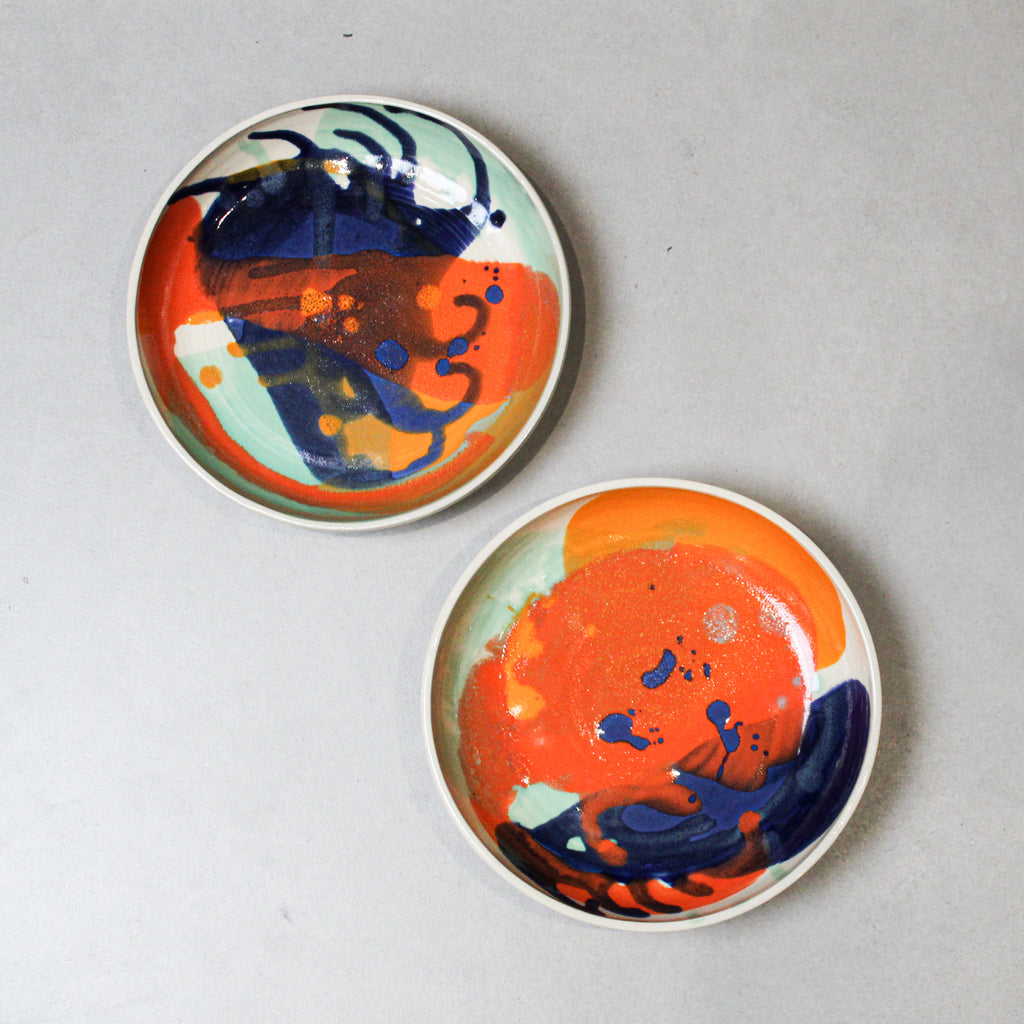 Two pottery bowls with brightly coloured abstract glaze in oranges and blues