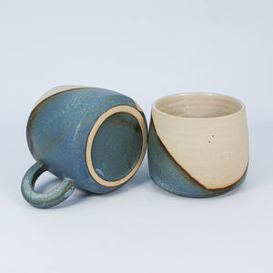 Two ceramic mugs, one lying on its side. White and blue glaze