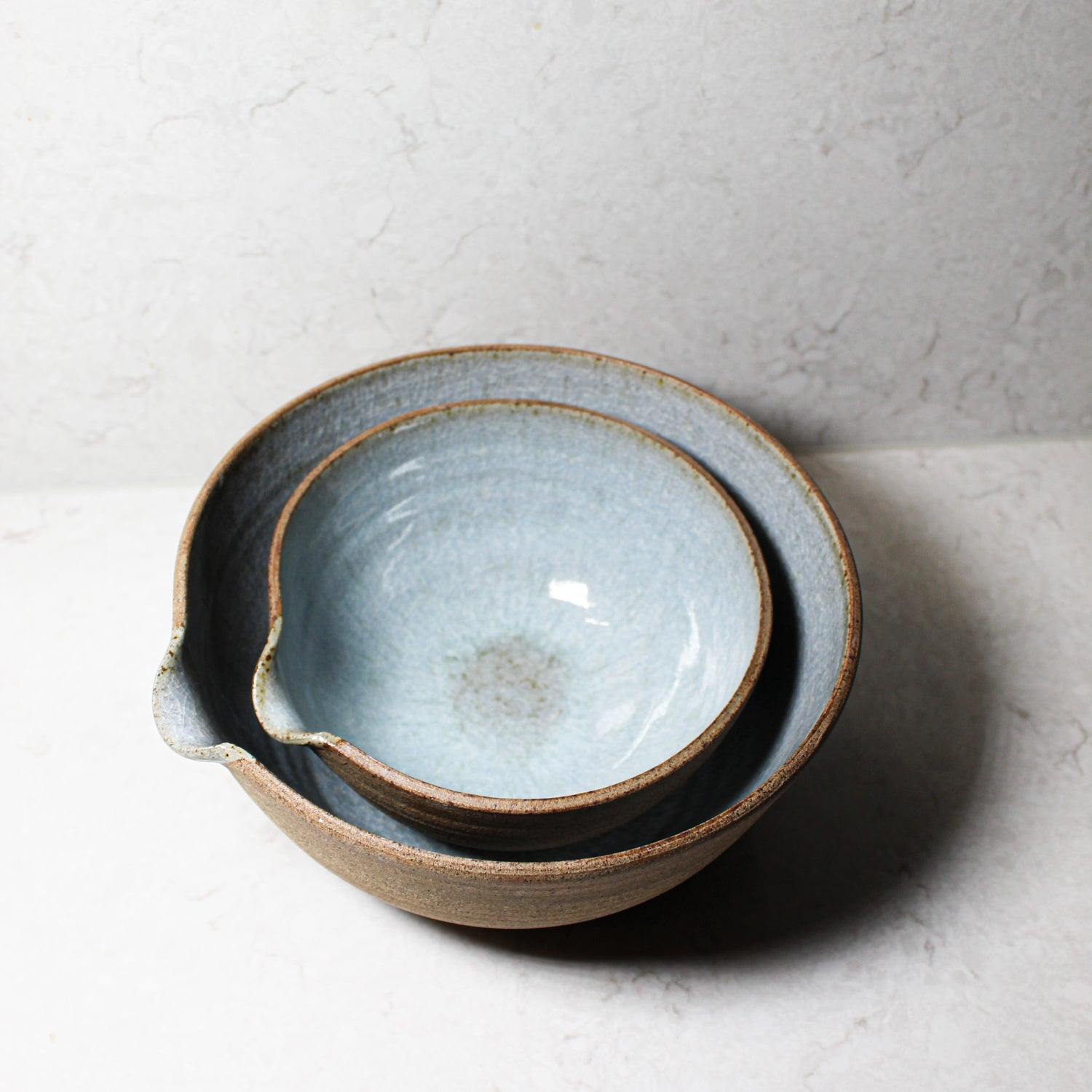 Two pottery pouring bowls stacked one inside the other
