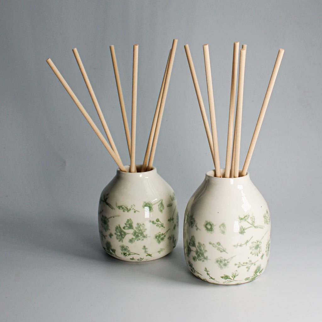 Pair of pottery reed diffusers. White with green wildflower pattern on