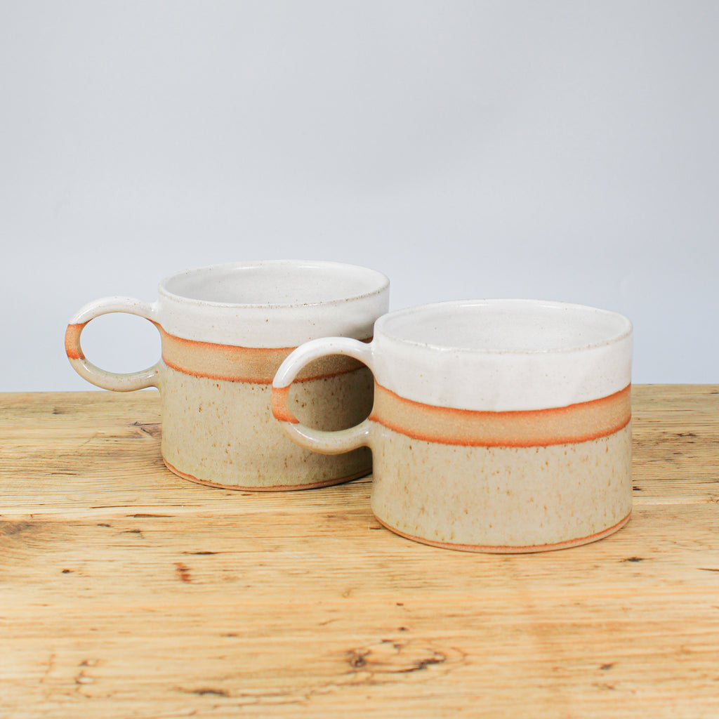 Two large pottery mugs on wooden table