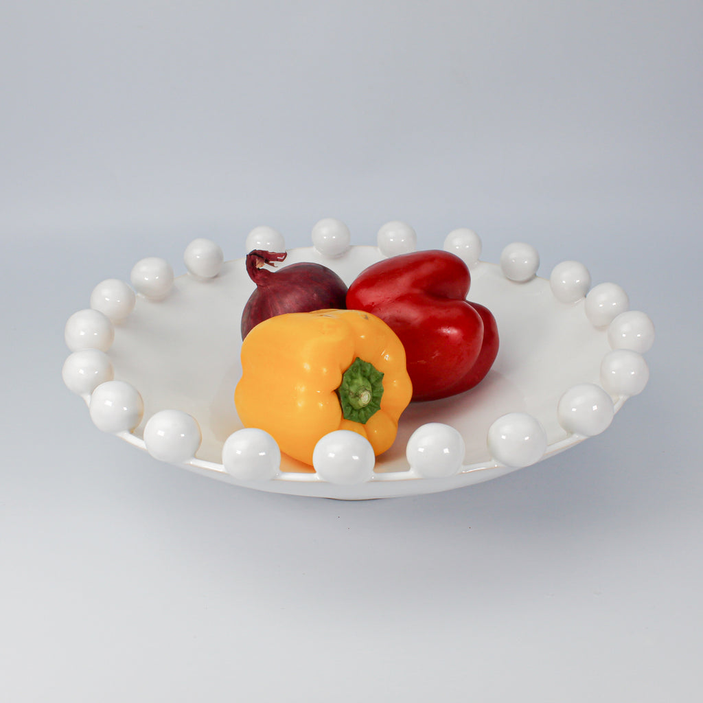 White ceramic bowl with bobbled edge. Yellow and red peppers and an onion inside
