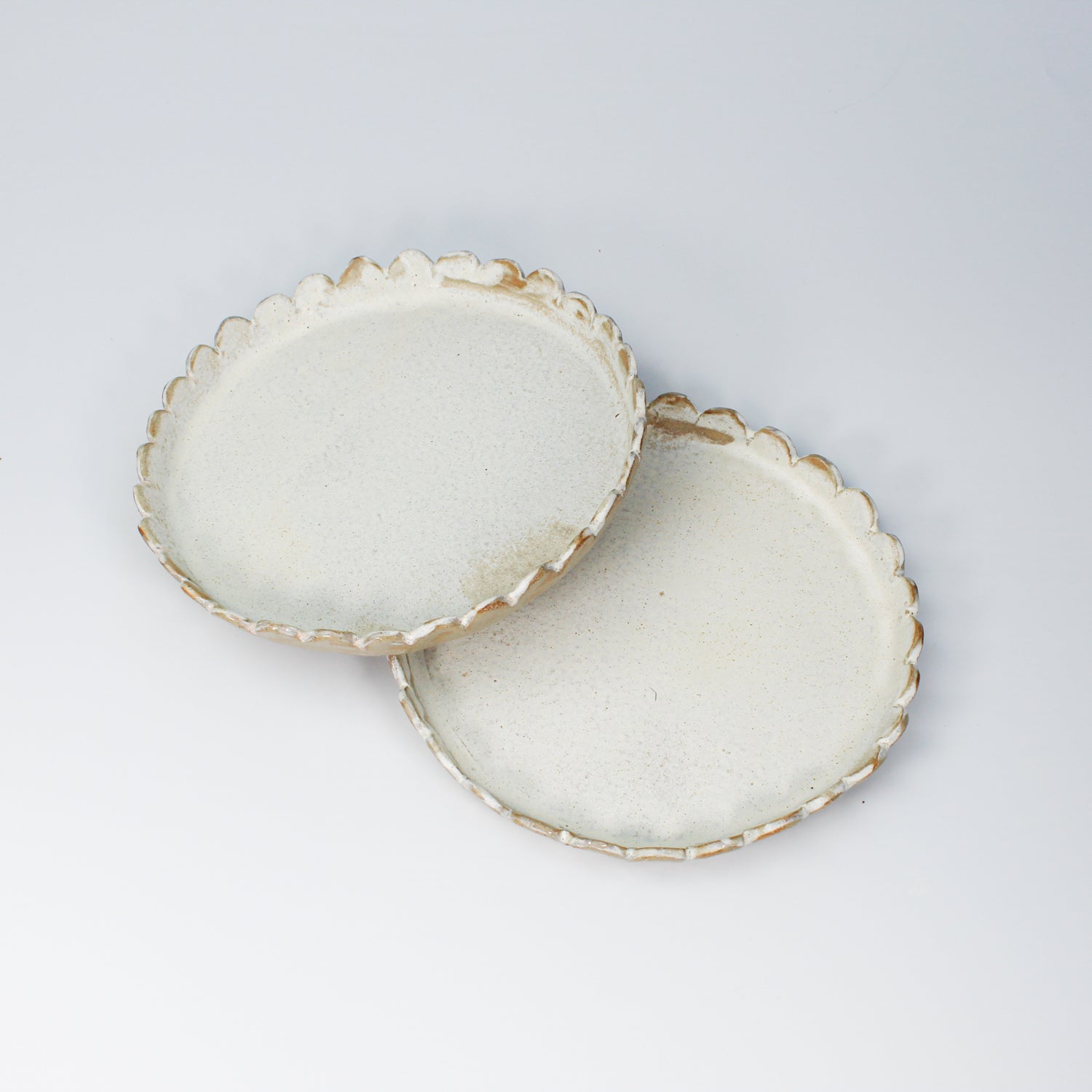 Pair of white ceramic side plates with scalloped edges