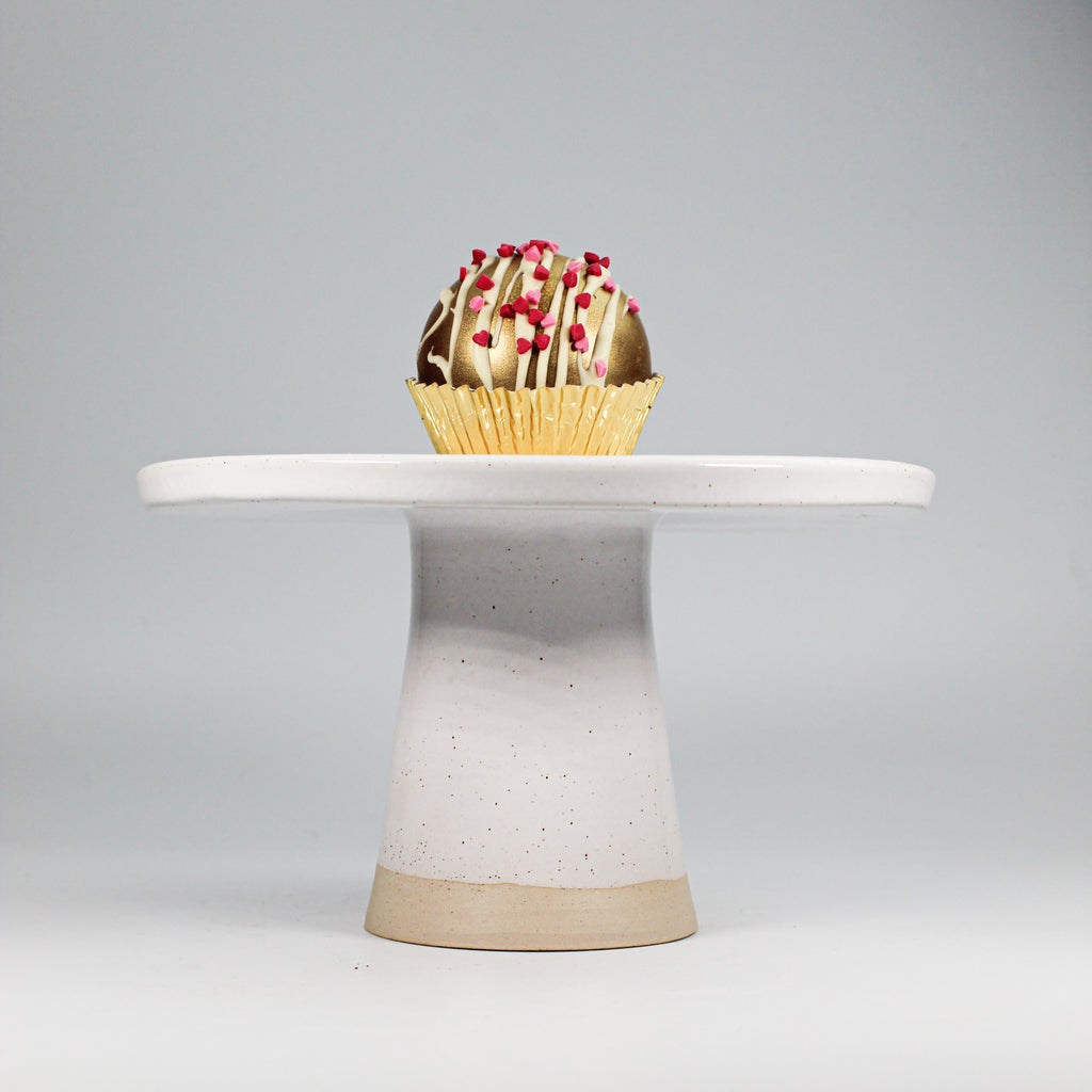White pottery  cake stand with cupcake on it