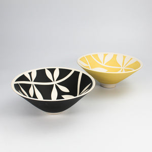 Two porcelain bowls with white leaf pattern. One bowl is yellow and the other is black.