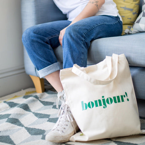 daisy sat on sofa with bonjour green slogan medium tote bag by her feet