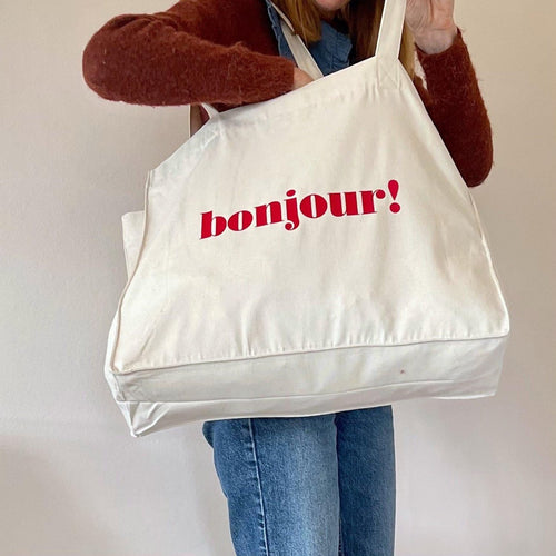 person looking inside large tote bag with bonjour slogan