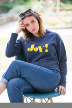 Load image into Gallery viewer, Daisy sitting crossed leg on chair wearing navy crewneck sweatshirt with yellow joy slogan