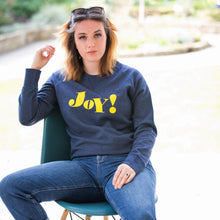 Load image into Gallery viewer, Daisy sat on chair wearing navy crewneck organic sweatshirt with yellow joy slogan