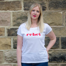 Load image into Gallery viewer, Hannah in short sleeve white t-shirt with red rebel slogan stone wall