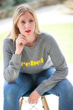 Load image into Gallery viewer, Hannah sat on chair wearing grey organic sweatshirt with rebel yellow slogan