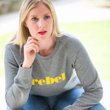 Load image into Gallery viewer, close up of Hannah sat on chair wearing grey crewneck sweatshirt with yellow rebel slogan