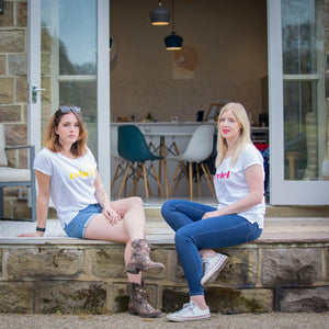 daisy and Hannah in  white t-shirts with bright coloured rebel slogan on patio